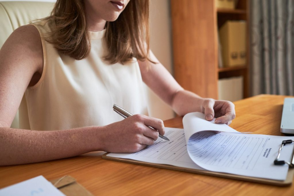 Woman signing paper on clipboard